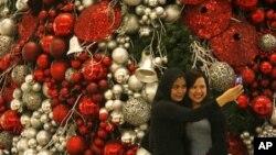ស្រ្តីពីរនាក់នេះឈរថតរូបនៅមុខ Christmas Tree។