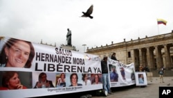 Demonstrators hold banners asking for the release of three journalists who are believe to have been taken hostage, during a sit-in in Bogota, Colombia, Wednesday, May 25, 2016.