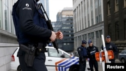 FILE - Belgian police officers secure an access to the federal police headquarters in Brussels, March 19, 2016, after Salah Abdeslam, the most-wanted fugitive from November's Paris attacks, was arrested after a shootout with police in Brussels on Friday.