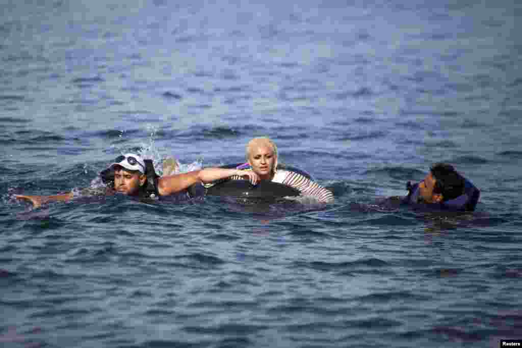 Syrian refugees swim towards a beach after abandoning a dinghy with a broken engine on the Greek island of Lesbos, Sept. 9, 2015. Greece asked the European Union for aid to prevent it being overwhelmed by refugees, as a minister said arrivals on Lesbos had swollen to three times as many as the island could handle.