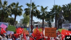 Warga melambaikan bendera nasional dalam protes melawan rencana untuk membangun kamp pengungsi di bawah perjanjian Uni Eropa-Turki di Dikili, Izmir, Turki (2/, April 2, 2016. Under the new deal refugees and migrants who arrived on Greek islands after March 2