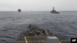 ກຳປັ່ນລົບຂອງກອງທັບເຮືອ ສະຫະລັດ ແມ່ນເຫັນໄດ້ ຈາກຫ້ອງຄວບຄຸມ ຂອງກຳປັ່ນພິຄາດ ຕິດລູກສອນໄຟນຳວິຖີ USS Spruance, ຢູ່ໃນທະເລຈີນໃຕ້, ວັນທີ 17 ຕຸລາ 2016, ໃນພາບນີ້ ທີ່ສະໜອງໂດຍ ກອງທັບເຮືອສະຫະລັດ.