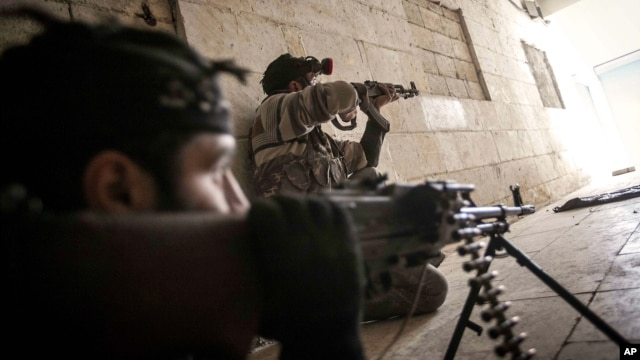 Free Syrian Army fighters aim their weapons at the entrance of a building during heavy clashes with government forces in Aleppo, Syria, December 5, 2012.
