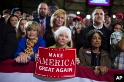 FILE - Supporters of Republican presidential candidate Donald Trump watch him speak during a campaign rally in Grand Rapids, Michigan, Oct. 31, 2016.