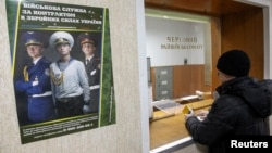 A man stands in front of a window at a district army recruiting office in Kiev March 2, 2014.