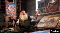 Michael Netzer, an American comics artist formerly named Mike Nasser, gestures during his interview with Reuters at his attic studio in his home in the Jewish settlement of Ofra in the Israeli-occupied West Bank