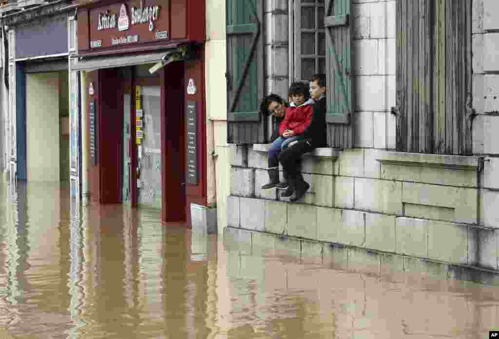 A mother and her children watch from their house the level of flooded water caused by heavy rain and thunder storms, in Salies-de-Bearn, southwestern France.