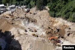 A general view shows heavy machinery working at an area affected by a mudslide in Santa Catarina Pinula, on the outskirts of Guatemala City, Oct. 6, 2015.