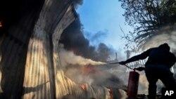 Un résident tente d'éteindre le feu sur le garage d'une église démarré par des habitants manifestants contre le remplacement de la candidat à la mairie, à Atteridgeville, Pretoria, le 21 juin 2016.