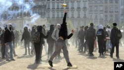 A young man throws a bottle against anti riot police, 21 October 2010, during clashes in Lyon, southern France, during a demonstration to protest against the pensions reform.