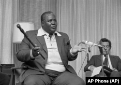 "FILE: Joshua Nkomo, co-leader of the Patriotic Front, tells newsmen that the Kissinger plan ""does not exist,"" in Geneva, Switzerland, Dec. 9, 1976. ""We cannot have the so-called Anglo-American plan imposed on the people of Zimbabwe,"" he said."