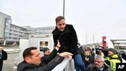 Wakil pemimpin Partai Sosialis Hungaria oposisi MSZP Zsolt Molnar (kiri) membantu wakil MSZP Tamas Harangozo menaiki pagar stasiun penyiaran pemerintah, MTVA, di Budapest, Hongaria, Senin, 17 Desember 2018.