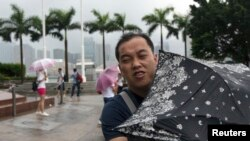 A man braves the wind at the Golden Bauhinia Square as Typhoon Utor approaches Hong Kong, August 14, 2013.