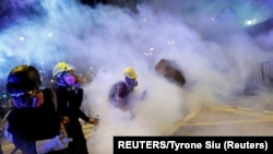 China, Hong Kong, Anti-extradition bill protesters walk among tear gas as they attend a march in Hong Kong