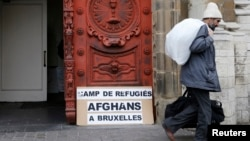 FILE - An Afghan asylum seeker walks out a church in central Brussels January 30, 2014.