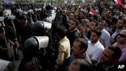 Supporters of Egyptian President Mohammed Morsi chant slogans as riot police, left, stand guard in front of the entrance of Egypt's top court, in Cairo, Egypt, Sunday, Dec. 2, 2012.