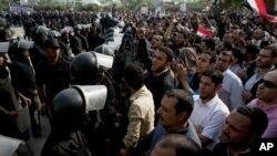 防暴警察守卫在开罗的埃及最高法院外应对呼喊口号的穆尔西总统支持者