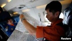 Seorang petugas penjagaan pantai Jepang mempelajari peta dalam pesawat Gulfstream V Jet yang terlibat dalam pencarian pesawat Malaysia Airlines yang hilang (15/3).