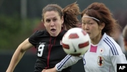 Japan's Mizuho Sakaguchi, right, and United States' Heather O'Reilly (9) chase the ball during the first half of a friendly soccer match in Cary, N.C., May 18, 2011.