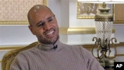 Seif al-Islam Gadhafi, son of Libyan Leader Moammar Gadhafi, smiles during a TV interview in Tripoli in this image taken from TV, March 16, 2011