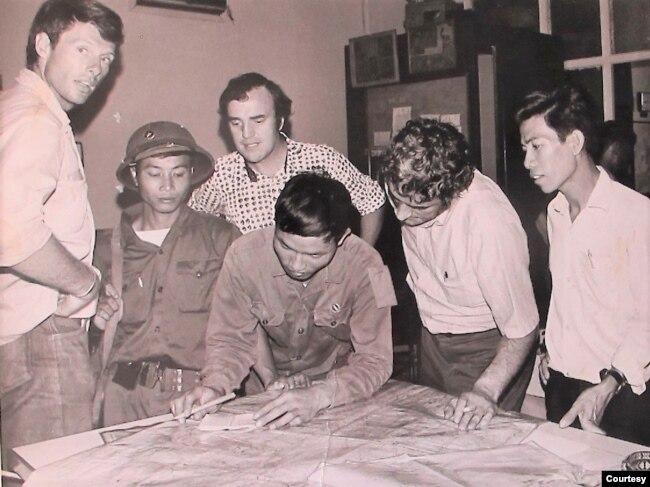 Một cán bộ cộng sản Bắc Việt cùng bảo vệ và thông dịch viên đến văn phòng AP Sài Gòn vào trưa 30 tháng Tư năm 1975 để làm việc với ba ký giả AP còn ở lại để tường trình việc thất thủ của Sài Gòn. Từ trái là ký giả Matt Franjola, giữa là Peter Arnett và trưởng văn phòng AP là George Esper. (Hình Peter Arnett cung cấp)