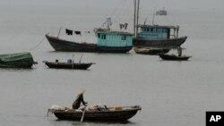 Vietnamese boatman rows past fishing boats, Ha Long Bay, northeast of Hanoi, Vietnam. (AP)