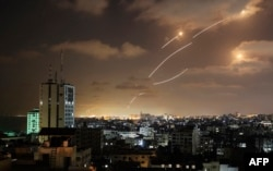 Rockets launched from the Gaza Strip, controlled by the Palestinian Hamas movement, are intercepted by Israel's Iron Dome aerial defence system on May 12, 2021. (Photo by MAHMUD HAMS / AFP