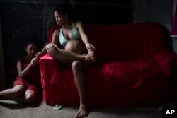 FILE - In this Jan. 29, 2016 photo, Tainara Lourenco, who is five months pregnant, sits inside her house at a slum in Recife, Brazil.