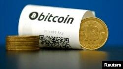"""Foto ilustrasi kertas Bitcoin (mata uang virtual) dengan kode """"QR"""" dan beberapa koin mata uang."""