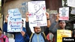 Orang-orang mengangkat poster untuk berunjuk rasa menentang klaim yang dibuat para pembicara yang mendiskreditkan teori yang dikemukakan oleh Isaac Newton dan Albert Einstein, pada Kongres Sains India ke-106 di Kolkata, India, 7 Januari 2019 (foto: Reuters/Stringer)