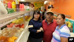 FILE - Diana Resendiz, from left, Alberto Resendiz and Maribel Resendiz pose for a photo at their business Mr. Tutis Fruties in Florida City, Florida, June 27, 2017.