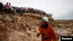 Petugas penyelamat di lokasi tempat helikopter militer Kamboja jatuh di pinggir Phnom Penh, sementara warga mengawasi (14/7).