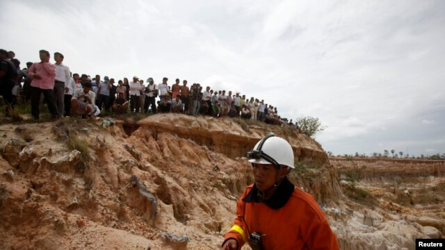 A rescue worker walks at the site where a Cambodian military helicopter crashed on the outskirts of Phnom Penh, July 14, 2014.