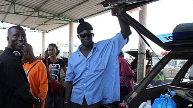 Papiss Sadio, left, stands next to another driver in the main truck garage in the southern Senegalese city, Ziguinchor