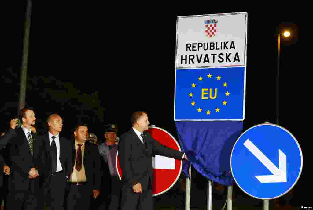 A Croatian official unveils a new EU border sign at Bajakovo border crossing between Serbia and Croatia, July 1, 2013.