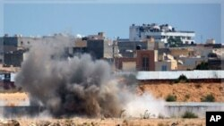 An explosion is seen near Muammar Gadhafi's main compound in the Bab al-Aziziya district in Tripoli, Libya, Tuesday, Aug. 23, 2011