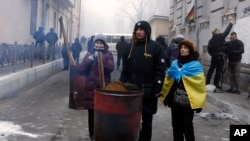 Supporters of former Georgian President Mikheil Saakashvili warm themselves at a fire as they gathered in a narrow street outside the police station where he was taken in Kyiv, Ukraine, Dec. 9, 2017.