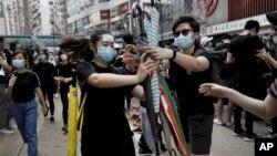 香港抗议者星期天(7月28日)在中环分发雨伞。美联社