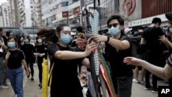 香港抗議者星期天(7月28日)在中環分發雨傘。美聯社