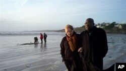 Franco-Togolese dual national politician Kofi Yamgnane walks with his wife Anne-Marie on the beach of Saint-Nic, western France, on 14 Nov 2009