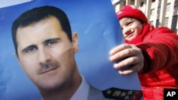 A pro-Syrian regime protester holds a portrait of Syrian President Bashar Assad during a demonstration to show support for their president, in Damascus, Syria. (File)