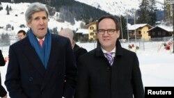 El secretario de Estado, John Kerry ,es saludado por el ambajador suizo, Philippe Guex, a su llegada a Davos.