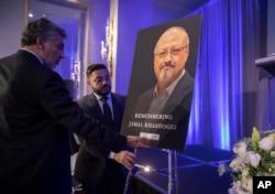 FILE - Mongi Dhaouadi, left, and Ahmed Bedier set up an image of slain Saudi journalist Jamal Khashoggi before an event to remember Khashoggi, a columnist for The Washington Post who was killed inside the Saudi Consulate in Istanbul.