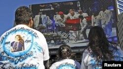 Admiradores de La Diva de la Banda observan en una pantalla los funerales de la cantante.