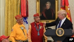 President Donald Trump, right, speaks about Sen. Elizabeth Warren, D-Mass., during a meeting with Navajo Code Talkers including, from left, Fleming Begaye Sr., Thomas Begay, and Peter MacDonald, in the Oval Office of the White House in Washington, Monday,