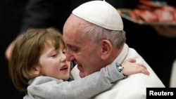 FILE - Pope Francis holds a child as he leads the weekly audience in Paul VI's hall at the Vatican, Jan. 20, 2016.