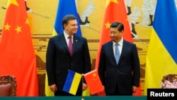 Ukraine's President Viktor Yanukovych (L) and Chinese President Xi Jinping attend a signing ceremony at the Great Hall of the People in Beijing, Dec. 5, 2013.