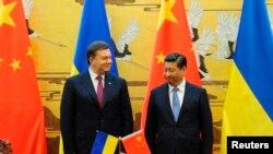 烏克蘭前總統亞努科維奇(左)去年訪問中國﹐與中國國家主席習近平會面。