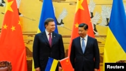 2013年12月5日,时任乌克兰总统的亚努科维奇在北京人民大会堂的签字仪式上和中国国家主席习近平在一起。如今,亚努科维奇已在抗议浪潮中被推翻并成为通缉对象。