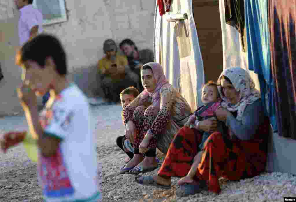 Kurdish refugees from the Syrian town of Kobani sit in a camp in Suruc, Oct. 5, 2014.